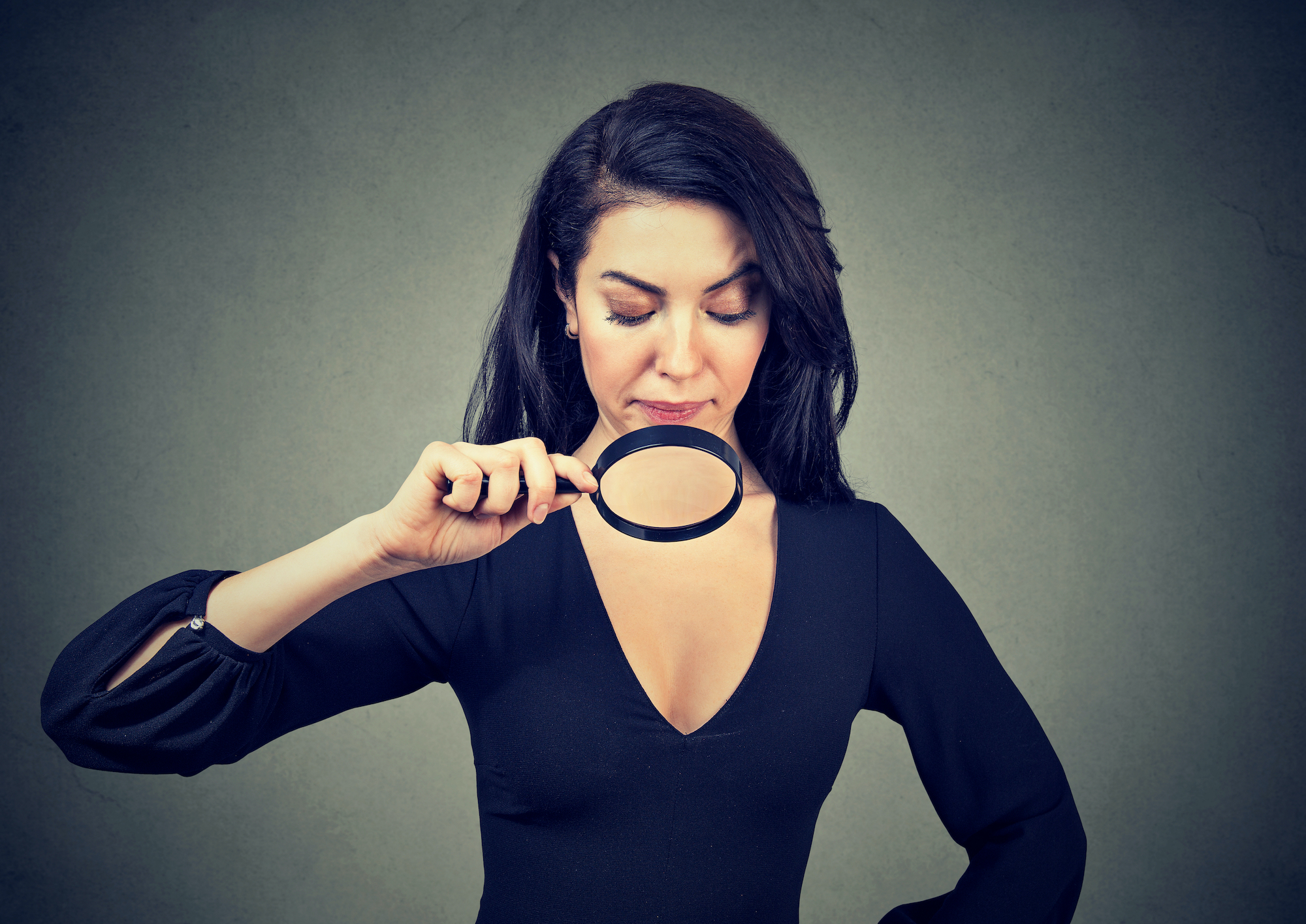 Young woman looking at her breasts through magnifying glass